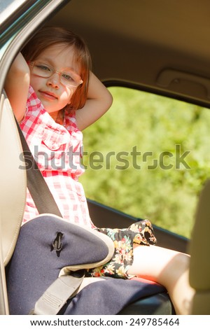 Road transportation and safety. Little girl child kid sitting in car seat and preparing to trip travel. - stock photo