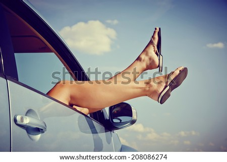 Road trip concept. Woman Hangs Her legs out of window in car. - stock photo