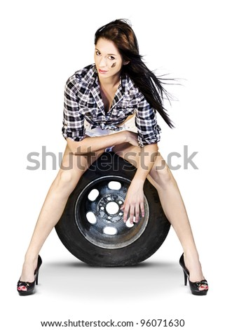 Road Trip Getaway. Sexy woman in shorts with long shapely legs sitting on a motor car tyre, conceptual studio image on white. - stock photo