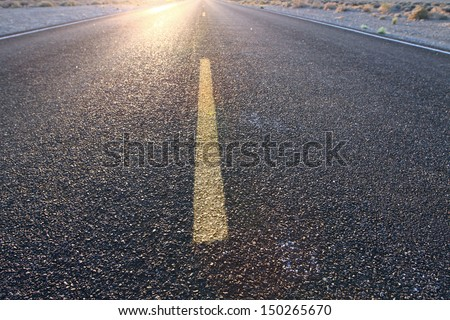 Road Trip on infinite roads through the wilderness at sunset - stock photo