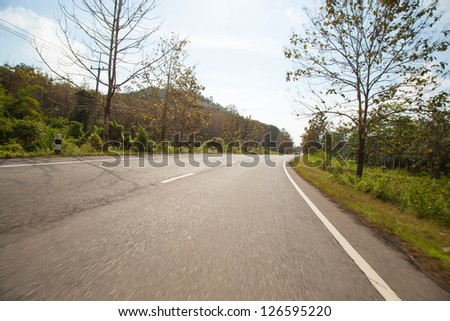 Road trip to the mountains. There are trees and mountains on both sides of the road along the way. - stock photo