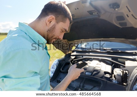 road trip, transport, travel, technology and people concept - young man with smartphone and open hood of broken car at countryside