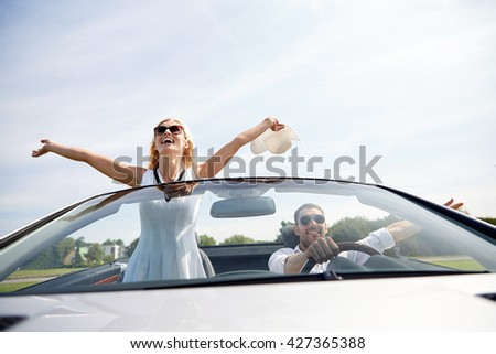 road trip, travel, dating, couple and people concept - happy man and woman driving in cabriolet car outdoors - stock photo