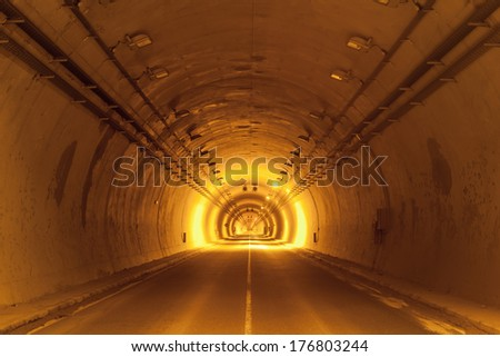 road tunnel tinted yellow with lights and road line