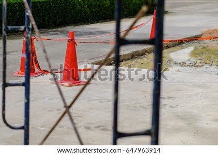 Road under construction with protected area by traffic cone and caution plastic tape