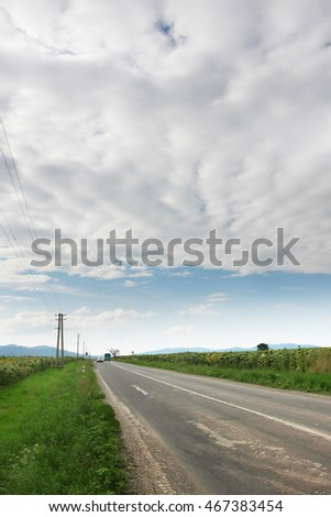 road under white clouds