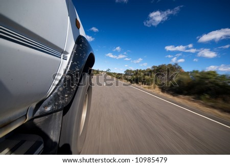 Road view of vehicle driving on country road - stock photo