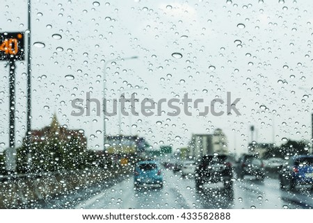 Road view through car window with rain drops, Driving in rain - stock photo