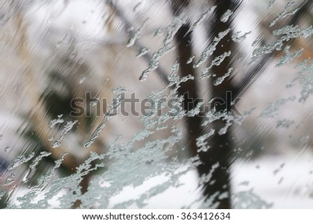 Road view through front car window with melted snowflakes and frost, artistic view