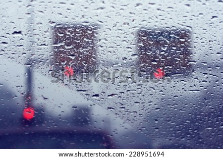 Road view through front car window with rain drops, drive carefully in heavy rain - stock photo