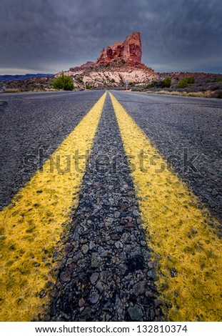 Road view towards a large monolith in Arches National Park, Utah - stock photo