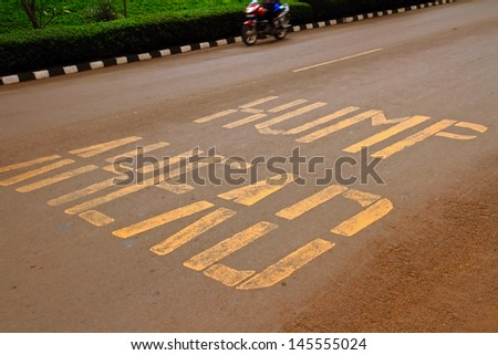 """Road warning painted on the ground warning that there is a """"hump ahead"""" in reference to a speed bump in Kigali,  Rwanda, Africa - stock photo"""