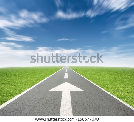 Road with arrow in landscape, motion blur on clouds - stock photo
