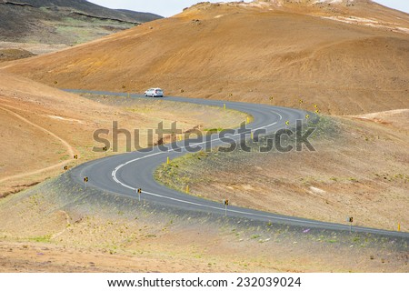 Road with cars leading through the mountain landscape looks like a big symmetric S letter, Iceland.  - stock photo