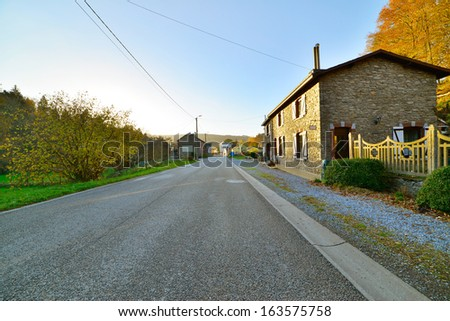 Road with houses and trees in autumn mountain landscape. Vresse sur Semois. Ardennes. Belgium. - stock photo