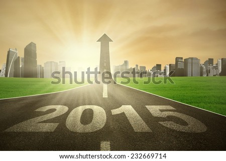 Road with number 2015 going up as an arrow with bright sun light, symbolizing the way for bright future - stock photo