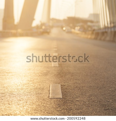 Road with sun lighting. Open road with no car traffic in the morning. - stock photo
