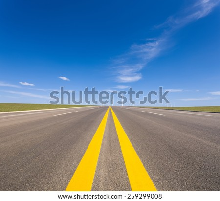 road with wind farm ,long highway stretching out into the distance - stock photo