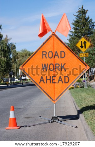 Road Work Ahead sign and orange cone standing in the street.