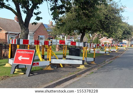 Road work warning signs and barriers in a street in England.  - stock photo