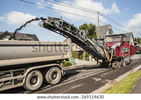 Road work with an asphalt road milling machine removing old pavement from a street surface  - stock photo