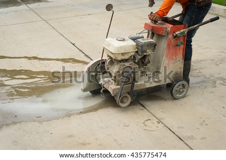 Road worker cutting asphalt road, working on the road reconstruction. saw cutting asphalt with water spraying to hold down dust. - stock photo