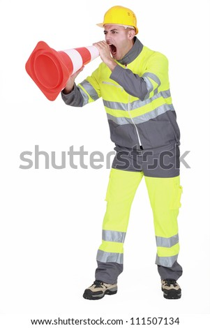 road worker shouting through a traffic cone - stock photo