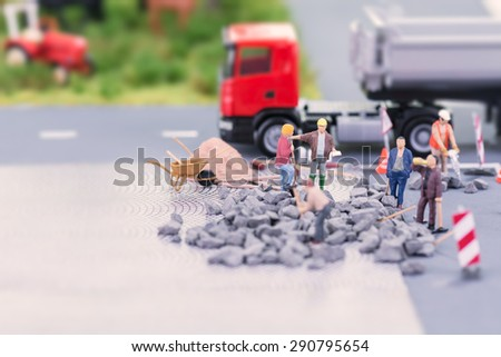 Road works with miniature workers close up - stock photo