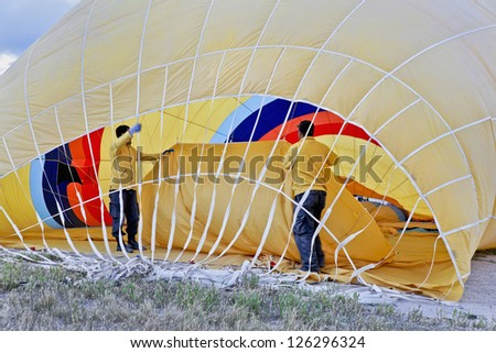 Roadies working inside a yellow hot air balloon making ready for a flight for tourist passengers in Cappadocia Turkey - stock photo