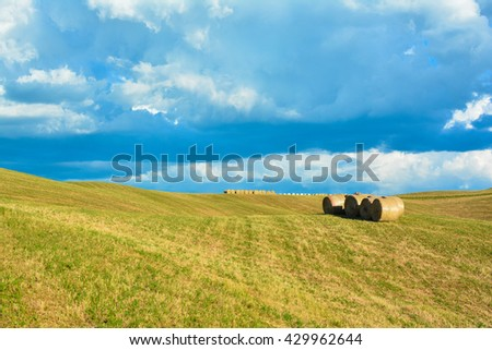 roads in the countryside in central Tuscany with cypresses fields of wheat and bales of hay on the Crete di Siena white clouds and blue sky - stock photo