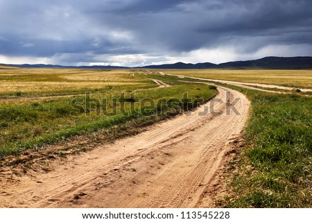 Roads in the desert steppes of Mongolia and the storm sky - stock photo