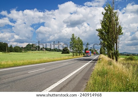 Roads with poplar alley in the countryside, come from afar two red trucks and a number of cars, in the background of green fields, villages, mountain with castle ruins - stock photo