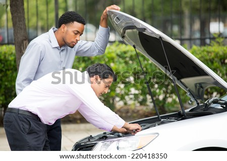Roadside assistance.  Closeup portrait, two frustrated guys trying to figure out how to fix broken down car on side of road, isolated green trees background - stock photo
