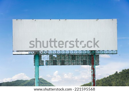 roadside billboard advertising display with blue sky and mountains - stock photo