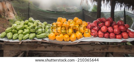 Roadside marketplace in north of Thailand. Red , Yellow bell peppers and Chayote fruit on wood stand - stock photo
