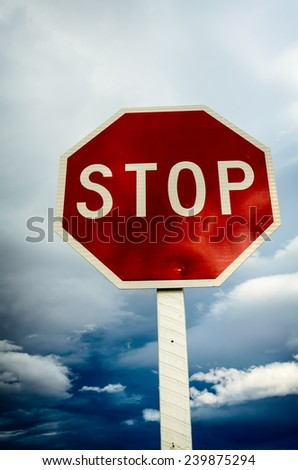 roadside red stop sign on a cloudy background. Sign isolated. - stock photo