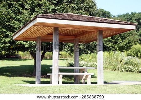 Roadside rest area with a picnic table and trees in background. There is a cover or canopy over the picnic table. - stock photo