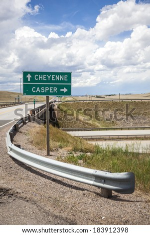 Roadside sign providing directions to Casper and Cheyenne, Wyoming along a rural Wyoming highway. - stock photo