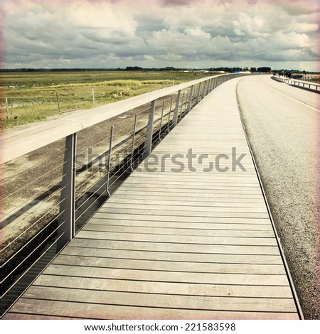 Roadside view on moody day in grunge and retro style. - stock photo