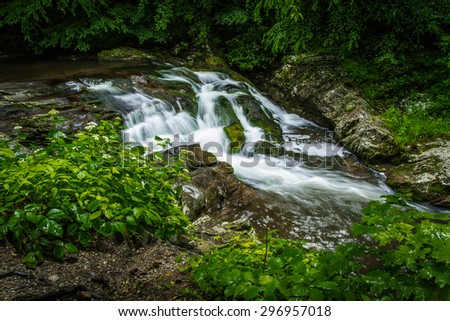 Roadside waterfall on the Little River Road. This scenic road is located within the Great Smoky Mountains National Park and features beautiful views of the Pigeon River with  waterfalls and cascades. - stock photo