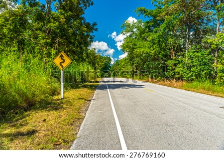 Roadway and yellow winding road sign in countryside of Thailand - stock photo