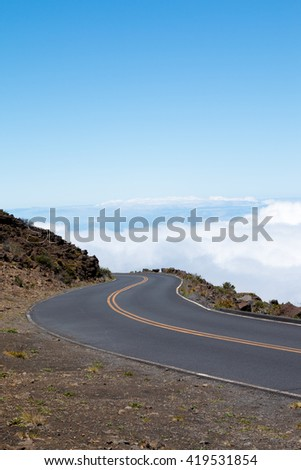 Roadway in the clouds on the way to the Haleakala Crater in Maui, Hawaii - stock photo