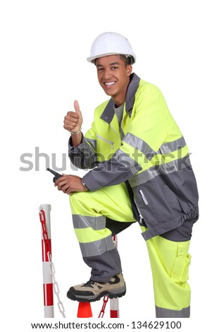 Roadworker in fluorescent jacket and trousers - stock photo