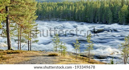 Roar from the big river. Spring and flood from the winter snow in a Nordic valley. Rock this side. - stock photo
