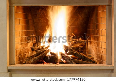 Roaring fire with bright orange flames blazing in a brick hearth for indoor heating, close up view - stock photo