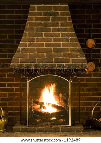 Roaring log fire of old English house with brickwork surround
