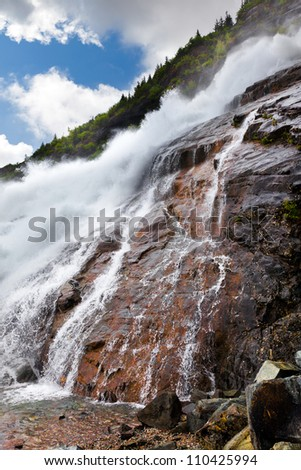Roaring waterfall at the Mendenhall glacier in Juneau, Alaska.  Also known as Nugget Falls or Nugget Creek Falls - stock photo