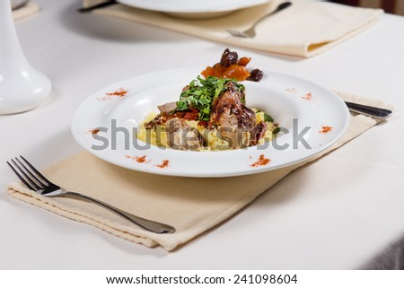 Roast beef and gravy with savory rice, mixed vegetables and herbs served at a restaurant table for a delicious dinner - stock photo