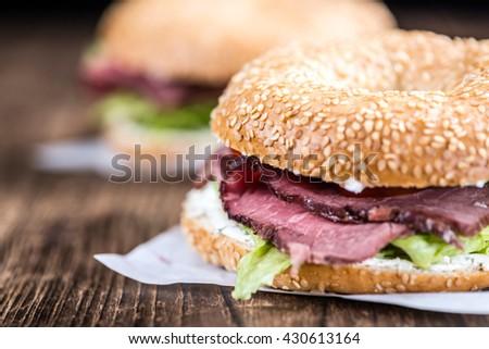 Roast Beef Bagel (selective focus) on vintage background (close-up shot) - stock photo