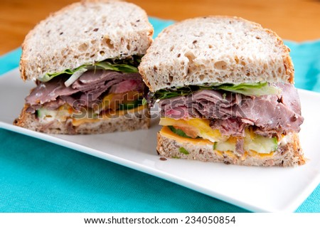 roast beef deli style sandwich on cracked whole wheat bread - stock photo